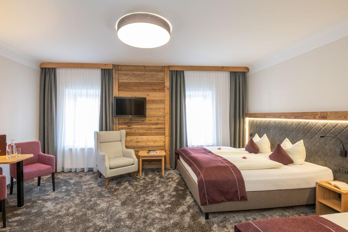 Dieses Komfort-Dreibettzimmer bietet ein Doppelbett (2 Matratzen) sowie ein extra 3. Bett, eine elegante Einrichtung mit Holz und Loden.