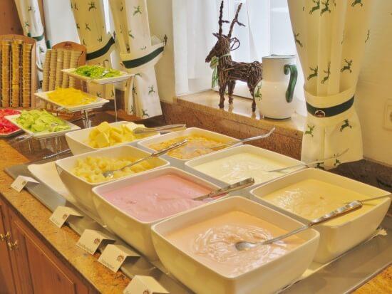 Verschiedene Joghurts, Früchtekompott sowie frisch geschnittenes Gemüse sind Teil des Frühstückbuffets
