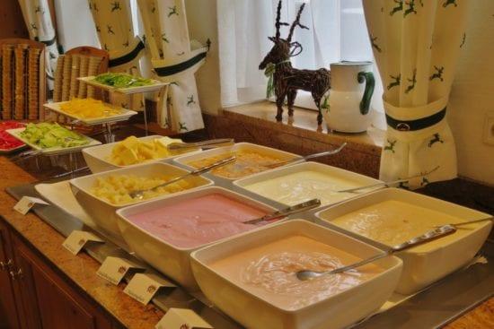 Detailansicht vom Frühstücksbuffet mit Naturjoghurt, Fruchtjoghurt, Fruchtsalat und frisch geschnittenem Gemüse