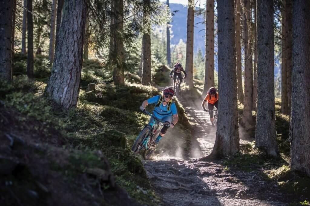 Mountainbiker bei einer rasanten Downhill Abfahrt durch den Wald im Bikepark Wagrain