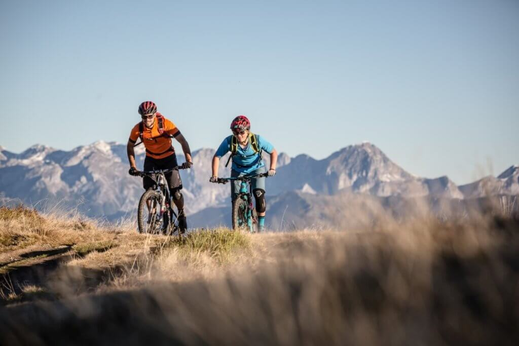 Mountainbiker auf dem Stoneman Taurista Anstieg zum Grießenkar mit Bergkulisse der Hohen Tauern im Hintergrund