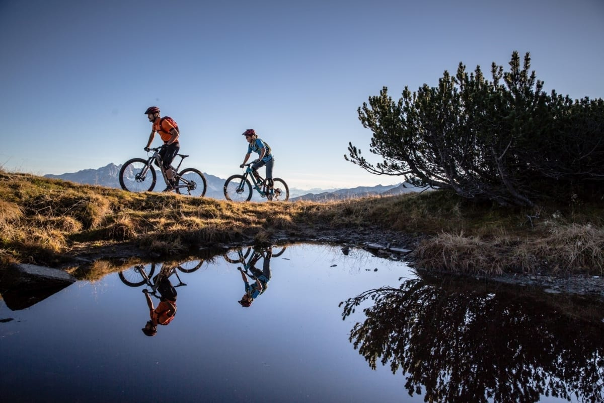 Mountainbiker am Stoneman Taurista Trail - Die Biker spiegeln sich im Wasser