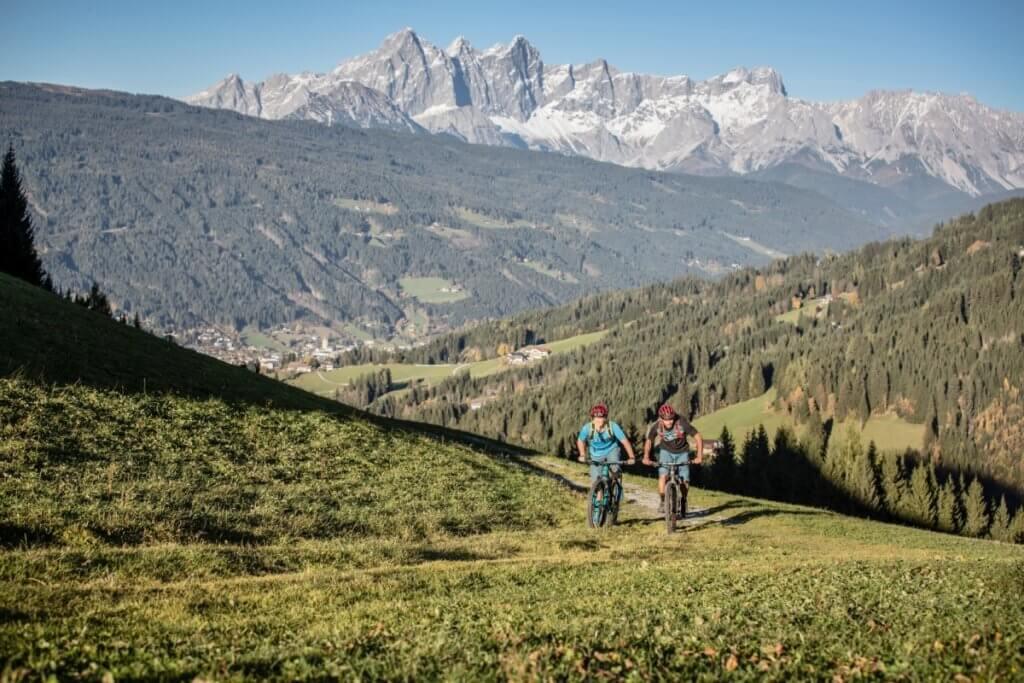 Mountainbiker beim Anstieg zum Sattelbauer mit Dachsteinmassiv im Hintergrund