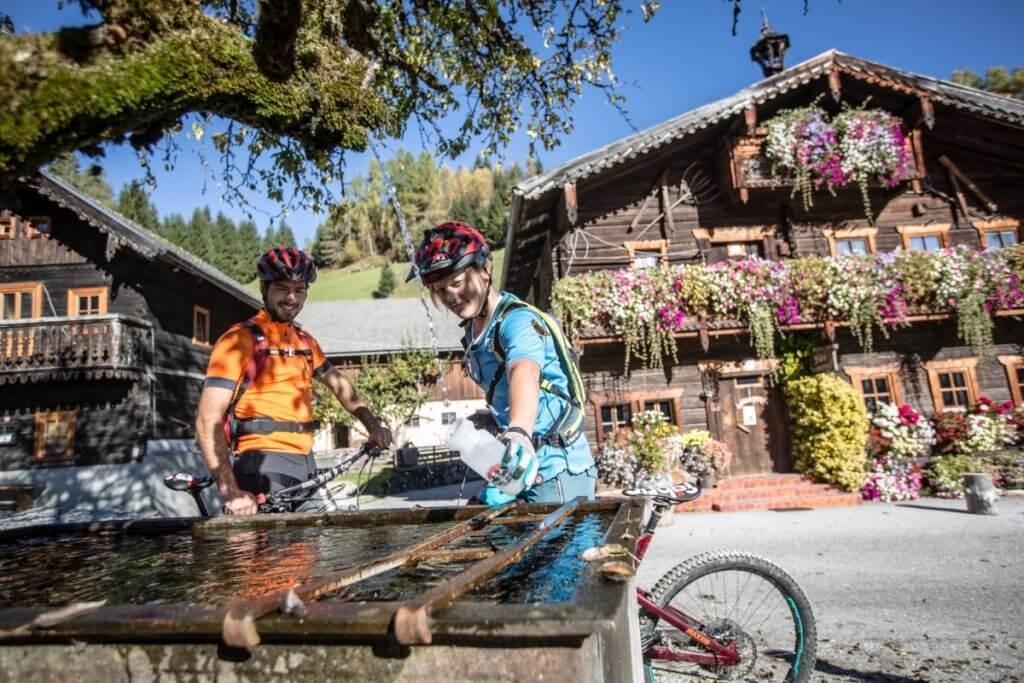 Mountainbiker am Wasserspender im Moadörfl mit Bauernhaus Idylle und Blumenpracht