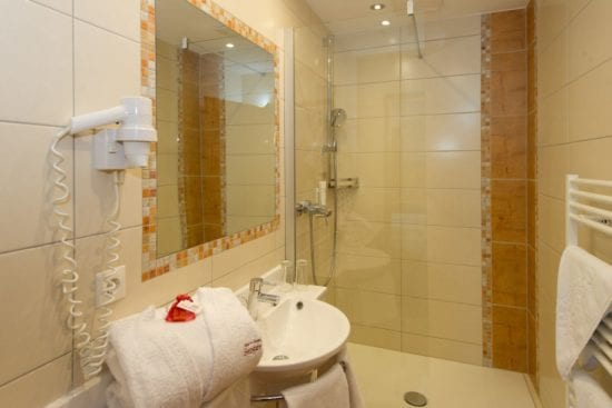 Badezimmer mit flachem Einstieg mit Glaswand, großem Spiegel, Waschbecken, Haarfön, WC separat