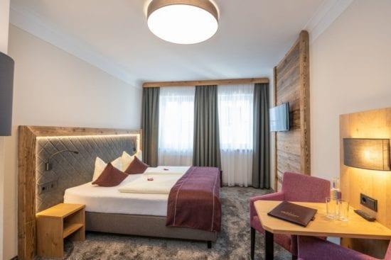 Doppelzimmer mit Boxspringbetten, Holz- und Lodenelementen, Teppichboden,