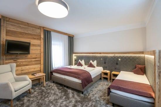 Die Dreibettzimmer im Stegerbräu bieten je nach Typ ein extra 3. Bett oder Sofabett für 3. Person. in Doppelbett und extra 3. Bett im Zimmer. Die Einrichtung mit Holz- und Loden oder klassich mit heller Buche