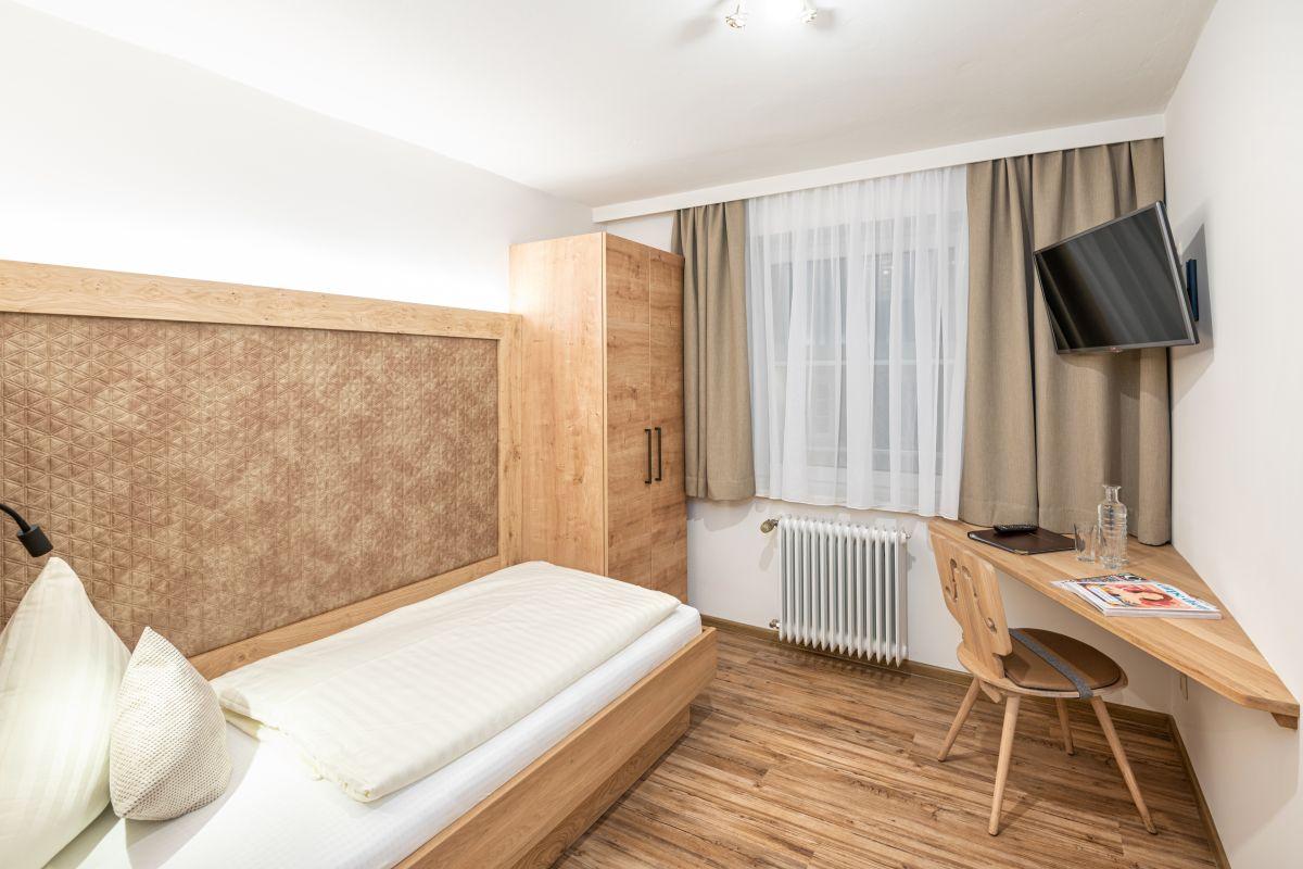 Einbettzimmer, schlicht-elegante Einrichtung mit Holzelementen, Einzelbett, Schreibablage, Stuhl, Schrank, Kabel-TV, Vinylboden