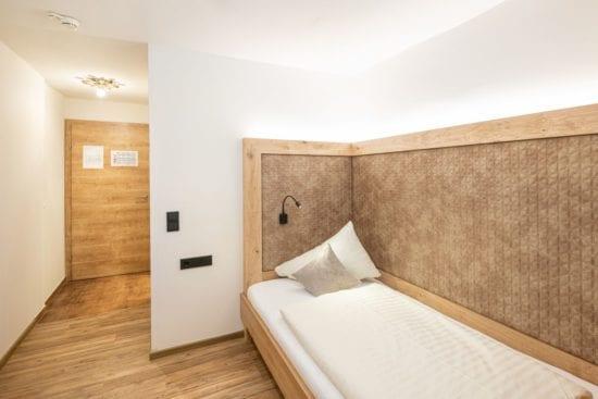 Teilansicht des Einbettzimmers mit Einzelbett. Das Zimmer hat einen Vinylboden