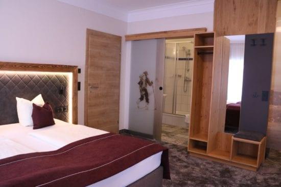 Teilansicht des Familienzimmers Bräu-Komfort. 1 Zimmer mit Doppelbett, getrenntem Schlafraum mit 2 Betten, 1 Badezimmer