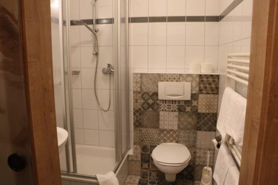 Badezimmer mit Duschkabine, Waschbecken, WC, Glasschiebetüre mit Motivbeschichtung