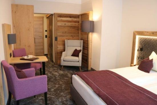 Ein Wohnbeispiel für ein Doppelzimmer mit neuem Zimmer-Outfit, viel Holz und angenehme Farben