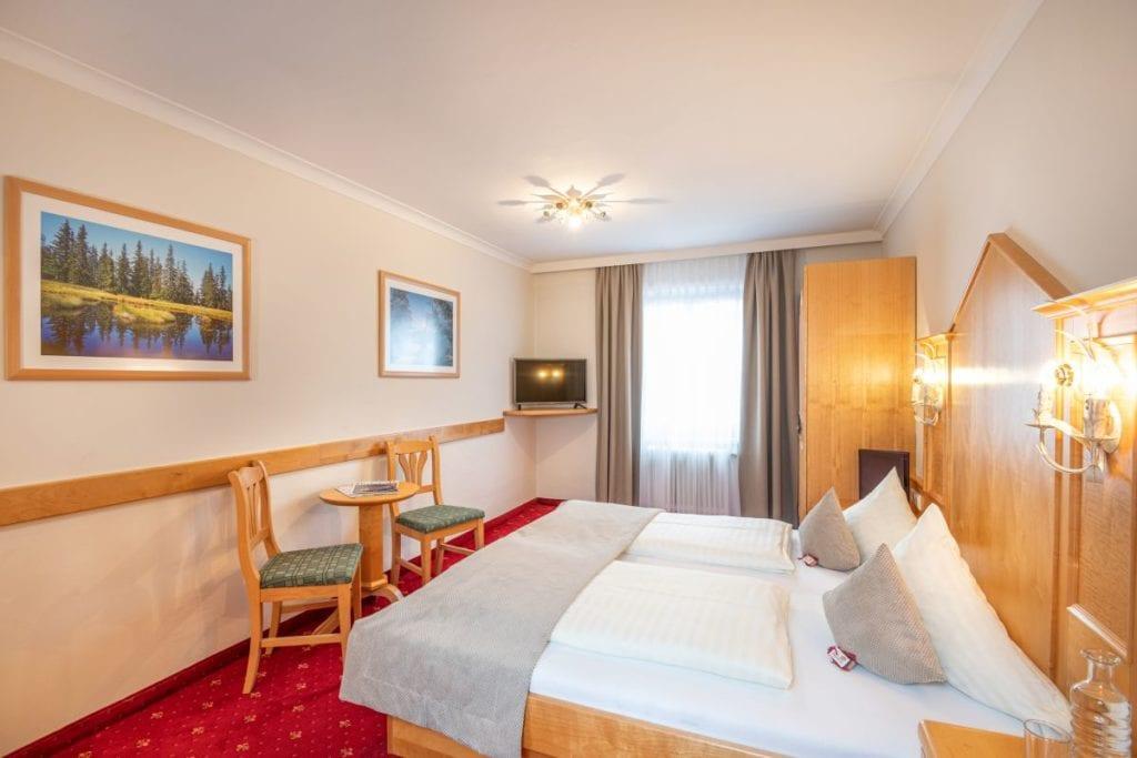 Wohnbeispiel eines Doppelzimmers, mit Einrichtung in heller Buche, Teppichboden, Kabel-TV mit Flachbildschirm, Tisch und 2 Stühlen, Zimmersafe.