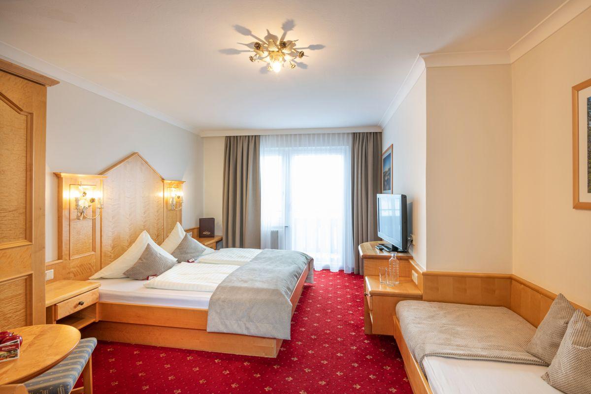 Ansicht eines Dreibettzimmers im Haupthaus, eingerichtet in heller Buche, Teppichboden, Doppelbett und extra 3.Bett, neues Badezimmer